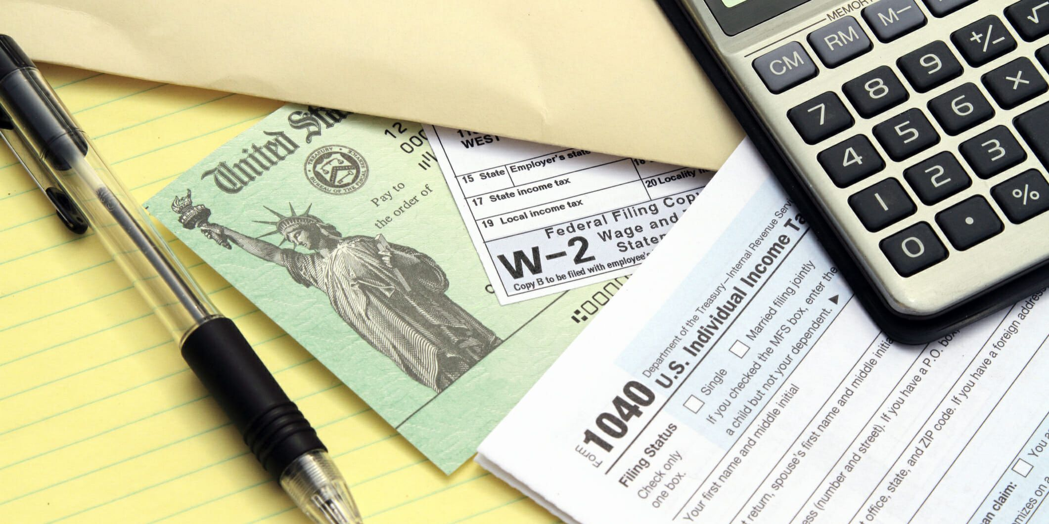 Tax forms with Treasury check. IRS tax forms 1040 and W-2. Tax preparation concept. Treasury check represents a tax refund. Calculator, pen and papers yellow note pad also visible.